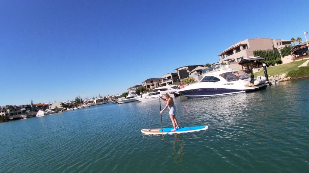 Woman paddle boarding in mindarie marina