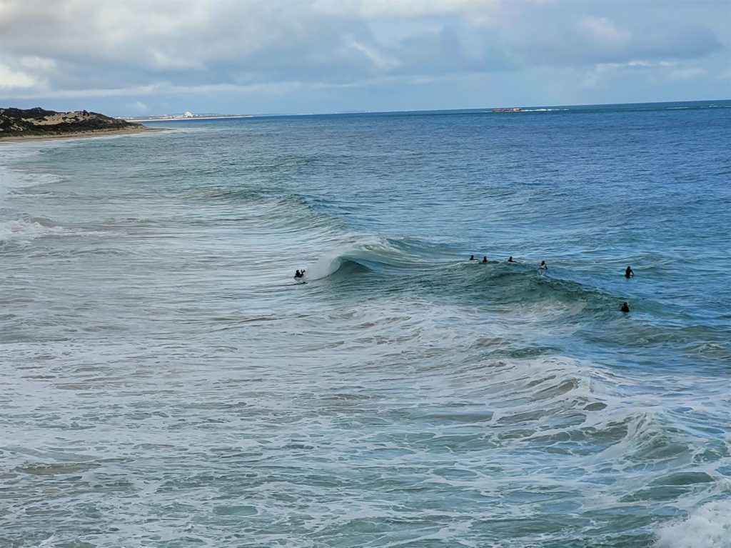 Surfers enjoying Claytons beach on a winters day